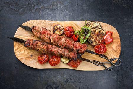 Traditional Russian shashlik on a barbecue skewer with vegetable and sumach as top view on a wooden cutting board with copy space Фото со стока - 129768738