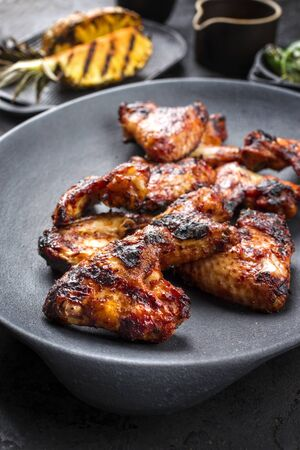 Exotically barbecue chicken wings with hot chili sauce, jalapeno and pineapple as closeup on a cast iron plate 스톡 콘텐츠