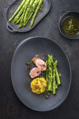 Fried Iberian pork fillet sliced with blanched green asparagus and potato gratin dauphinois with spice as top view on a cast iron design plate