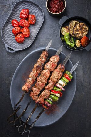 Traditional Russian shashlik on a barbecue skewer with vegetable and sumach paste as top view on a modern design plate Фото со стока - 129768858