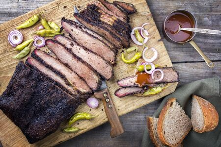 Traditional smoked barbecue wagyu beef brisket offered with farmhouse bread as top view on an old cutting board with Louisiana sauce, onion rings and peperoni