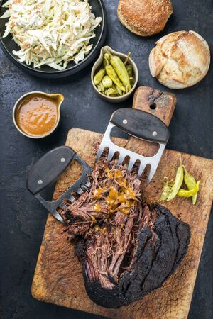 Traditional barbecue wagyu pulled beef with coleslaw and sandwich as top view on a rustic cutting board Stock Photo