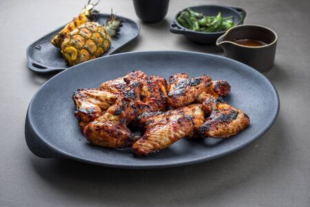 Exotically barbecue chicken wings with hot chili sauce, jalapeno and pineapple as closeup on a cast iron plate Stock Photo - 129768873