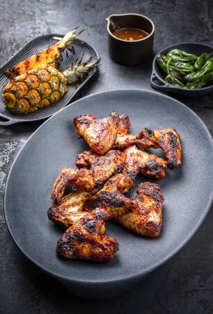 Exotically barbecue chicken wings with hot chili sauce, jalapeno and pineapple as top view on a cast iron plate Stock Photo