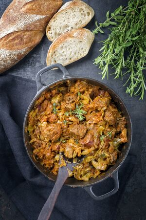 Traditional Polish kraut stew bigos with sausage, meat and mushrooms as top view in a cast iron pot on an old wooden table