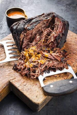 Traditional barbecue wagyu pulled beef with spicy sauce as closeup on a rustic cutting board