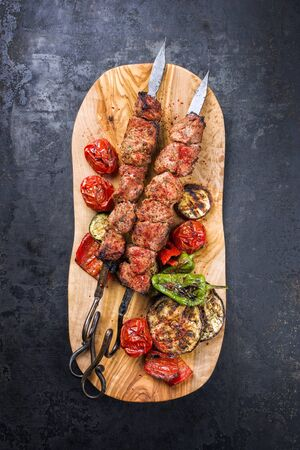 Traditional Russian shashlik on a barbecue skewer with vegetable and sumach as top view on a wooden cutting board with copy space Фото со стока - 129769043