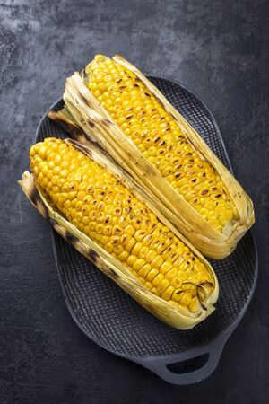 Traditional barbecue corn green as closeup on a cast iron design plate with copy space