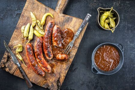 Traditional barbecue German Bratwurst with hot sauce and pepperoni as top view on an old cutting board with copy space Standard-Bild