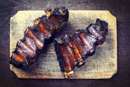 Barbecue chuck beef ribs with hot marinade as top view on a wooden cutting board