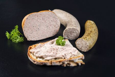 Traditional German meat paste with farmhouse bread offered as closeup on a black board with copy space Zdjęcie Seryjne