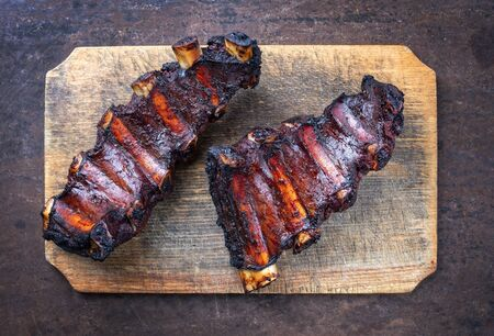 Barbecue chuck beef ribs with hot marinade as top view on a wooden cutting board with copy space
