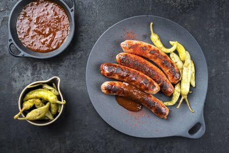 Traditional barbecue German Bratwurst with hot sauce and pepperoni as top view on a modern design cast iron plate