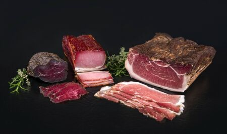 Traditional cured and smoked ham offered on a black board with copy space