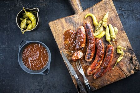 Traditional barbecue German Bratwurst with hot sauce and pepperoni as top view on an old cutting board