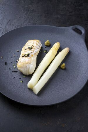 Fried Danish skrei cod fish filet with white asparagus, wasabi and nori as top view on a modern design plate with copy space