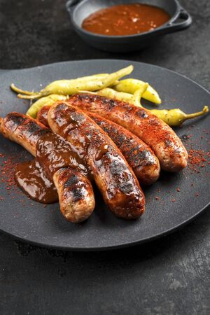 Traditional barbecue German Bratwurst with hot sauce and pepperoni as closeup on a modern design cast iron plate