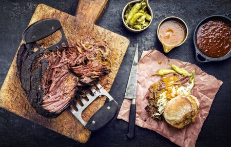 Traditional barbecue wagyu pulled beef with coleslaw and sandwich as top view on a rustic cutting board 스톡 콘텐츠