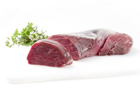 Dry aged beef fillet steak natural with a bouquet garni as closeup on white background with copy space – isolated