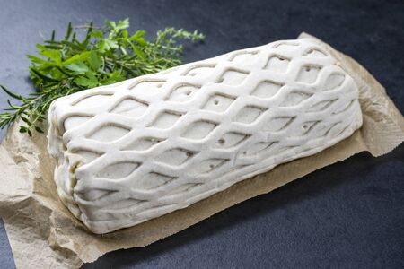 Raw Kasseler pork steak as piece in puff pastry with herbs as closeup offered on brown paper and black background with copy space