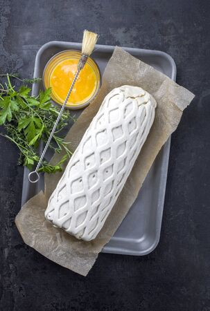 Raw Kasseler pork steak as piece in puff pastry and egg yolks as top view offered on a griddle with herbs