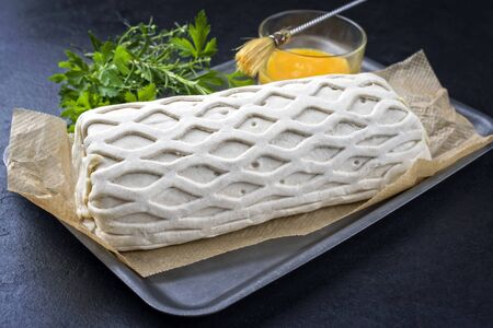 Raw Kasseler pork steak as piece in puff pastry and egg yolks as closeup offered on a griddle with herbs on a black board