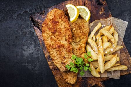 Fried Wiener schnitzel from veal topside with French fries and lemon slice as top view on an old rustic cutting board with copy space 免版税图像