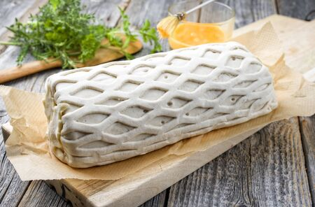Raw Kasseler pork steak as piece in puff pastry and egg yolks as closeup offered on a wooden cutting board with herbs