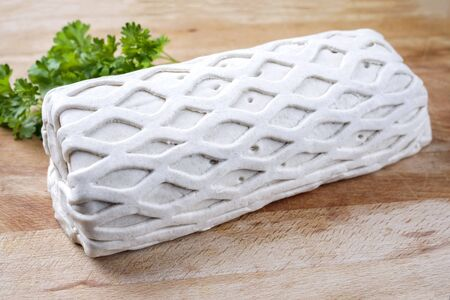 Raw Kasseler pork steak as piece in puff pastry as closeup offered on a wooden cutting board with with herbs