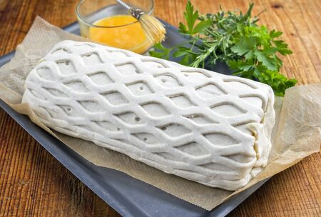 Raw Kasseler pork steak as piece in puff pastry and egg yolks as closeup offered on a griddle with herbs