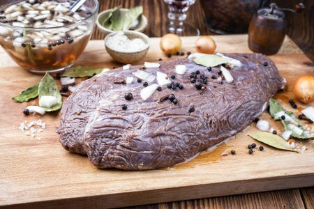 Marinated traditional German Sauerbraten from beef with onion and spice as closeup on a rustic wooden cutting board  Imagens
