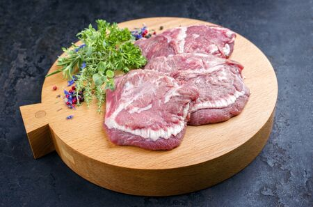 Traditional German raw beef cheeks offered as closeup with herb and spice on a modern design wooden cutting board