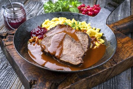 Traditional braised marinated German Sauerbraten from beef with spaetzle and cranberry jam in spicy brown sauce as closeup in a rustic wrought iron plate