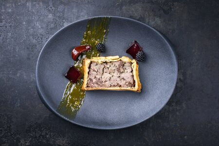 French pate en croute with goose liver, fruit relish and jelly as top view on a modern design cast iron plate  Фото со стока