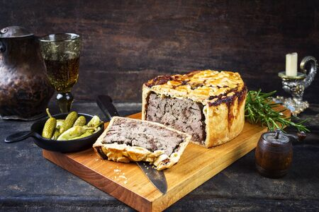 Traditional French Pate en croute with goose liver as closeup with gherkin and pepperoni on a modern design cutting board