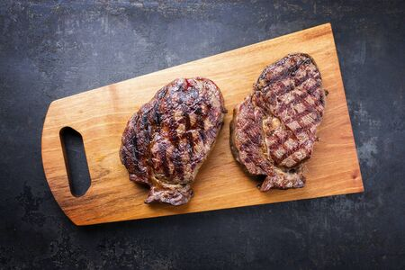 Traditional barbecue dry aged wagyu entrecote beef steak as top view on modern design wooden cutting board