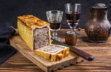Traditional French Pate en croute with goose meat and liver as closeup with red wine on a wooden board 写真素材