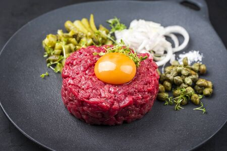 Gourmet tartar raw from beef fillet with yellow of the egg and gherkin with capers and onion rings as closeup on modern design plate Foto de archivo