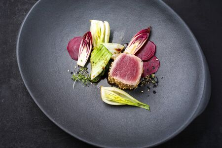 Japanese gourmet fried tuna fish steak tataki with pak choi, witloof and red beet offered as closeup on a modern design plate