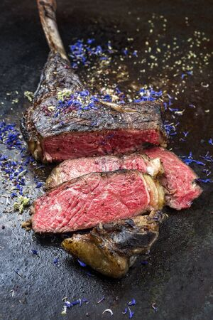 Barbecue dry aged wagyu tomahawk steak with herbs as closeup on black rustic board