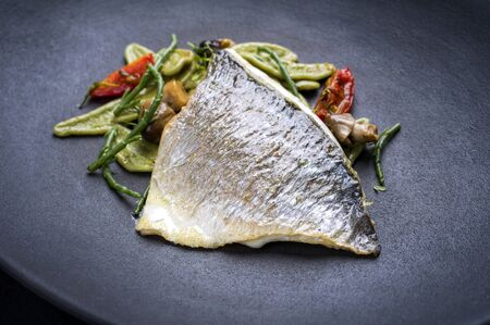Gourmet fried Italian gilthead fish filet with spinach pasta, glasswort and tomatoes as closeup on a modern design plate