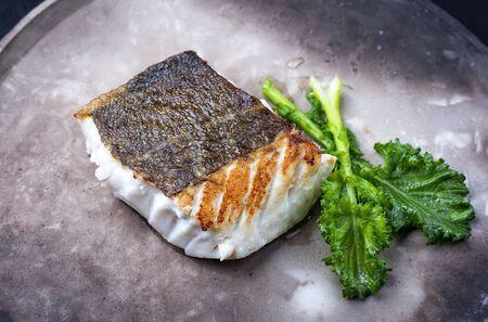 Gourmet fried European skrei cod fish filet with rapini broccoli rabe as closeup on a modern design plate
