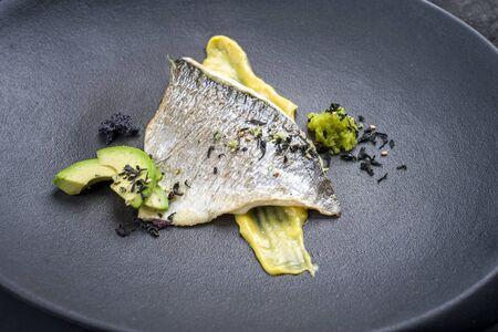Gourmet fried gilthead fish filet with caviar, avocado slices and mustard mango creme as closeup on a modern design plate Archivio Fotografico