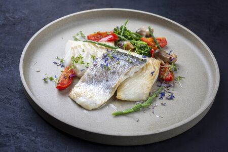 Gourmet fried Italian cod fish filet with broccoli, glasswort and tomatoes as closeup on a modern design plate