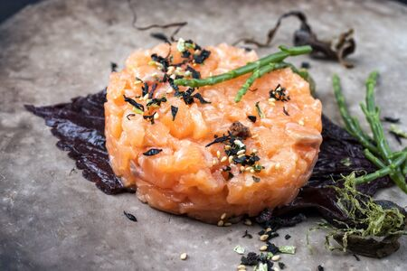 Gourmet salmon fish tartar raw from salmon fillet with glasswort, nori and Japanese spice as closeup on a modern design plate
