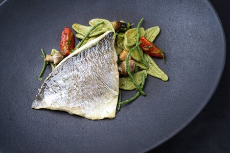 Gourmet fried Italian gilthead fish filet with spinach pasta, glasswort and tomatoes as top view on a modern design plate Banque d'images
