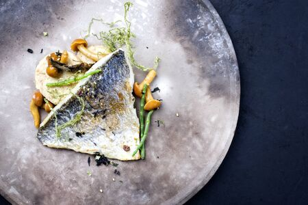 Gourmet fried gilthead fish filet with sliced dumpling, glasswort and algae as top view on a modern design plate with copy space right