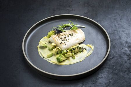 Gourmet fried cod fish filet with caviar, avocado slices and mustard mango creme as closeup on a modern design plate