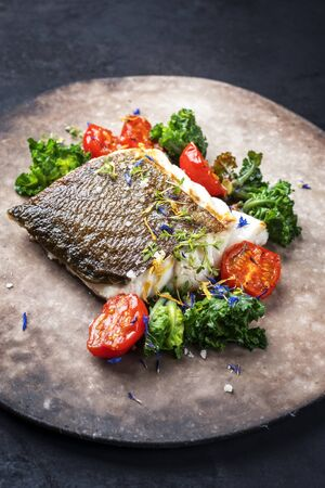 Gourmet fried European skrei cod fish filet with kalette and tomatoes as closeup on a modern design plate with copy space Archivio Fotografico