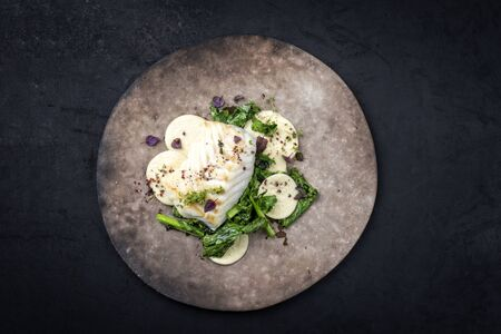 Gourmet fried European skrei cod fish filet with rapini broccoli rabe and creoxetti pasta as top view on a modern design plate with copy space Banque d'images